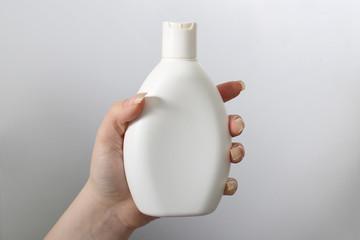 Hand holding white bottle on the white background horisontal