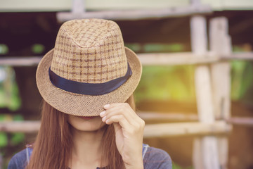 Hipster woman holding brown hat in front of her faces ,she was wearing jeans,in a cows farm.