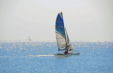 Blue sailing boat near Istanbul with shiny sea reflections