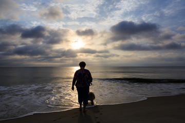 Silhouette of woman on beach in early morning walking dog