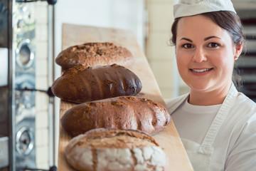 Bäcker frau zeigt frisches Brot auf Brett in Bäckerei und schaut stolz in die Kamera