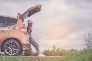 Hipster woman traveler sitting on hatchback car with nature background in vintage tone.She looking at the sky on sunset.