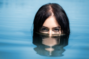 A sexy woman or girl, floating in the water, only the eyes are visible from the water. Concept of leisure, travel and vacation