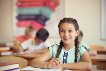 Happy clever children learning in classroom