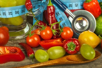 Glasses of water and a tailor's meter. Fruits and vegetables. The concept of weight loss. Healthy diet.