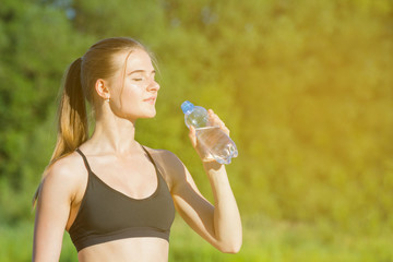 Portrait of a beautiful girl in fitness clothes outdoors, with a bottle of water in her hand