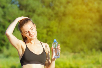 Portrait of a beautiful woman in fitness clothes outdoors, with a bottle of water in her hand