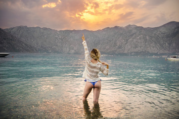 Gorgeous fit woman, knee deep in sea water , holding one arm up in the air. Happy young attractive  woman on vacation, beautiful mountains in background