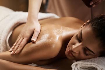 Close up of beautiful african girl enjoying massage in spa salon.
