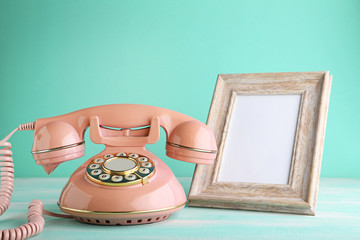 Pink retro telephone with photo frame on wooden table