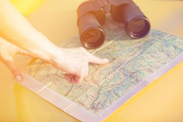 Female hand show a point at map near a binoculars