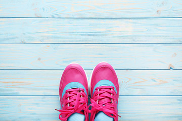 Pink sport shoes on blue wooden table