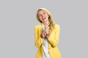 Portrait of happy young businesswoman. Image of joyful young woman dressed in yellow jacket posing over grey background.