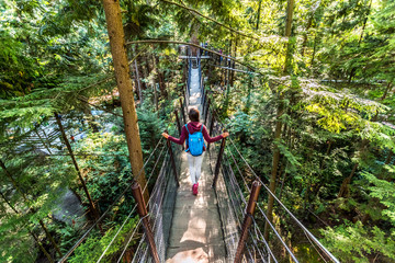 Canada travel tourist woman walking in famous attraction Capilano Suspension Bridge in North Vancouver, British Columbia, canadian vacation destination for tourism. Fotomurales