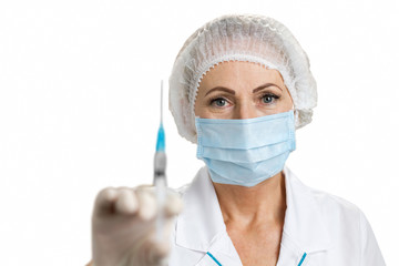 Close up of female doctor in mask. Mature nurse in protective cap and face mask holding syringe close up, white background.