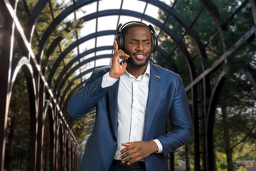 Afro american businessman with headphones outdoors. Black man in formal wear listening to music and enjoying a beat. Dark skinned man smiling with headset.