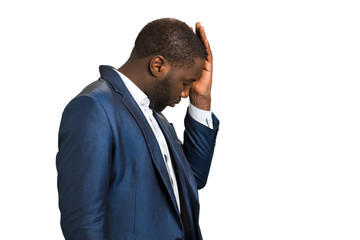 Businessman with closed eyes and headache. Beard black manager touching his head with hand, side photo. Dissapointed and frustrated afro american businessman feeling headache.