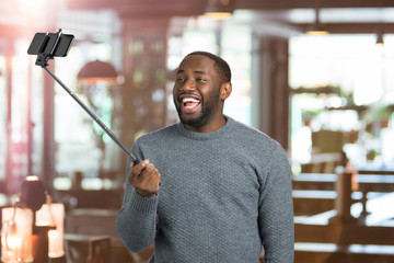 Joyful guy taking picture with selfie stick. Happy young man taking selfie holding monopod on blurred background. Taking sweet moments with selfie stick.
