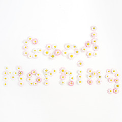 Quote Good Morning made of white and pink chamomile daisy flowers on white background. Flat lay, top view. Floral background. Pattern of flower buds.
