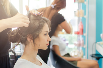 Hairdresser combing hair bun
