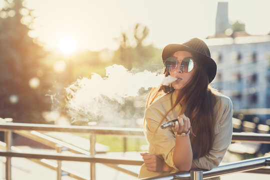 Pretty young hipster woman in black hat vape ecig, vaping device at the sunset. Toned image.