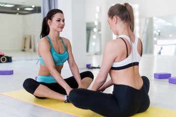 Two pretty slim girls wearing sportswear sitting in front of each other in butterfly pose or purna titali asana practicing yoga during group session indoors