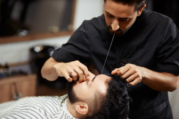 Barber grooming young man in chair