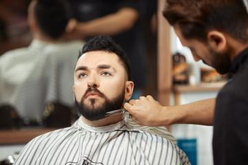 Barber grooming man in chair