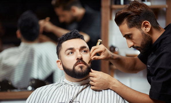 Concentrated barber working with man
