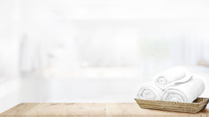 Towels in basket on top wood table with copy space on blurred bathroom background. .Products Display Concept.
