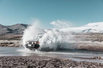 vehículo todoterreno cruzando un arroyo en el altiplano. Chile