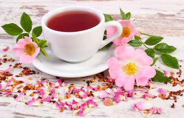 Cup of hot tea with wild rose flower on old rustic wooden board