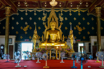 Principal buddha image in shinning golden color sitting in the decorative main hall with apostle monk image standing on both sides, Wat Asokaram