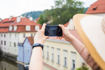 woman taking picture of Old Town in Prague with a smartphone.