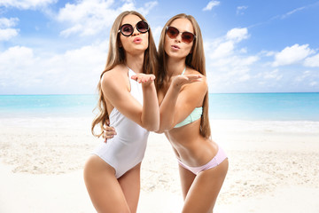 Two beautiful girls relaxing on the beach and blowing air-kisses