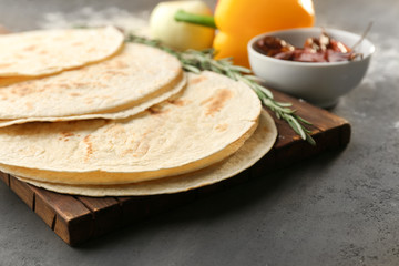 Board with delicious tortillas on kitchen table