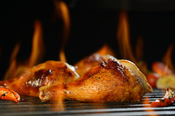 Wall Mural - Grilled chicken leg on the flaming grill