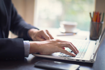Businessman at work. Close-up of man working on laptop at the wooden desk