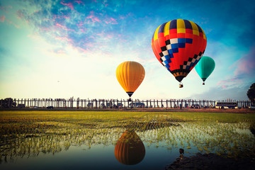 Colorful hot-air balloons flying over the u-bein bridge at burma
