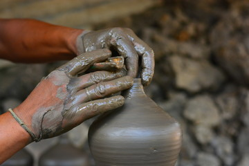 close up on hands making pots on pottery wheel
