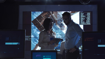 Side view of man and woman communicating in space flight control center. Some elements of this image furnished by NASA.