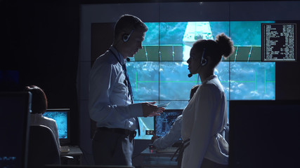 Side view of multiracial man and woman communicating in space flight control center. Elements of this image furnished by NASA.