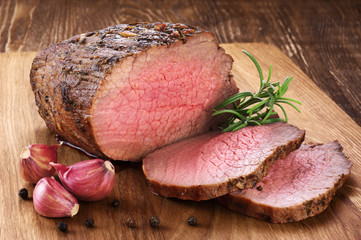 Door stickers Meat Baked meat, garlic and rosemary on a wooden background. Roast beef.