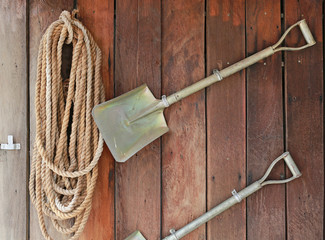 Shovel and rope hanging on the wooden plank wall. Garden decoration. Gardening tools.