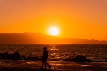 Blick auf wunderschönen Sonnenuntergang und Menschen am Meer