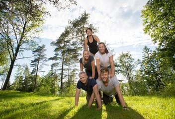 Portrait Of Multiethnic Friends Making Human Pyramid On Field