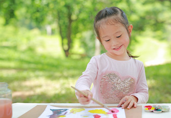 Cute little girl with painted hands in the park, Education art concept.