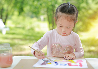 asian child girl sitting at a table in a summer garden painting with paintbrush, Education art concept.