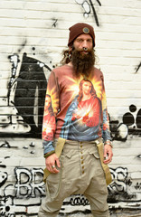 fashionable Men with Jesus Shirt in front of an grafitti wall