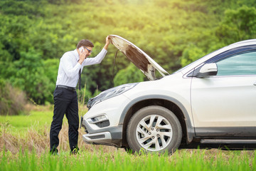 Full length of worried businessman by broken down car at countryside, man besides he broken car talking on the cell phone